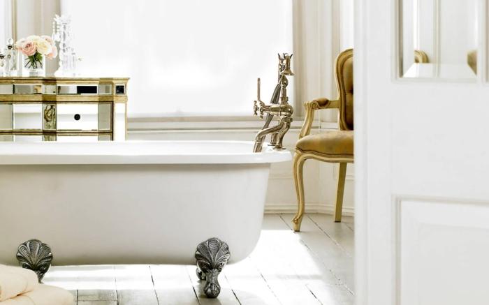 decoración baño de lujo, mueble baño, bañera con patas de garra plateados, sillón, armario en dorado, rosas y ventana grande