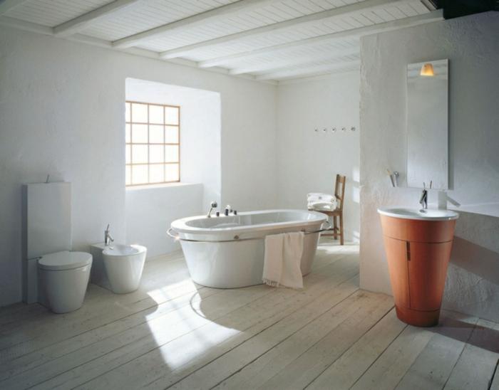 cuarto de baño grande decorado en blanco con bañera exenta y paredes en blanco, muebles de baño rusticos y suelo de madera