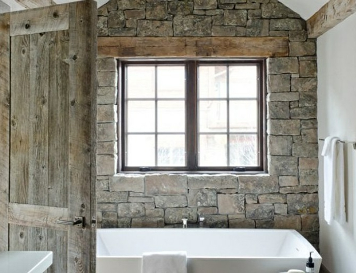 muebles de baño rusticos, puerta de madera y pared revestida de piedra con vigas de madera, muebles y paredes en blanco
