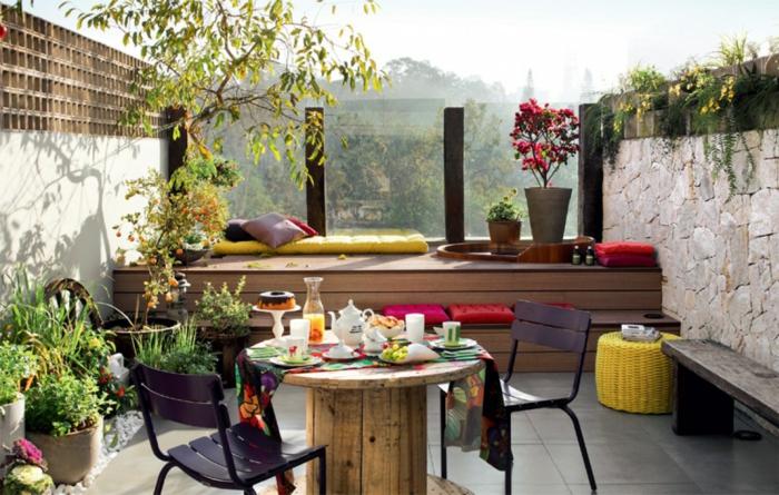 pequeña terraza coqueta, cómo decorar terrazas de pequeño tamaño, muchos objetos decorativos, mesa de madera y macetas con plantas verdes