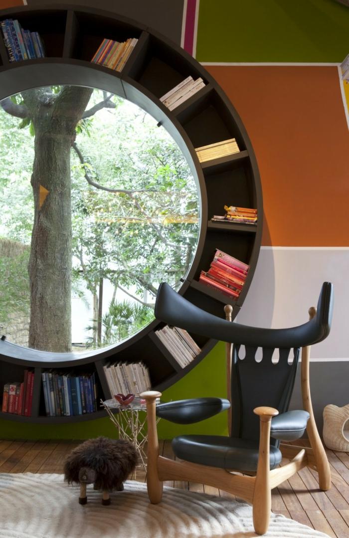 estanterias para libros, idea de librería redonda con ventana, silla moderna de madera y piel, tapete, suelo con tarima, pared en cuadrados de color, naranja, verde y gris+