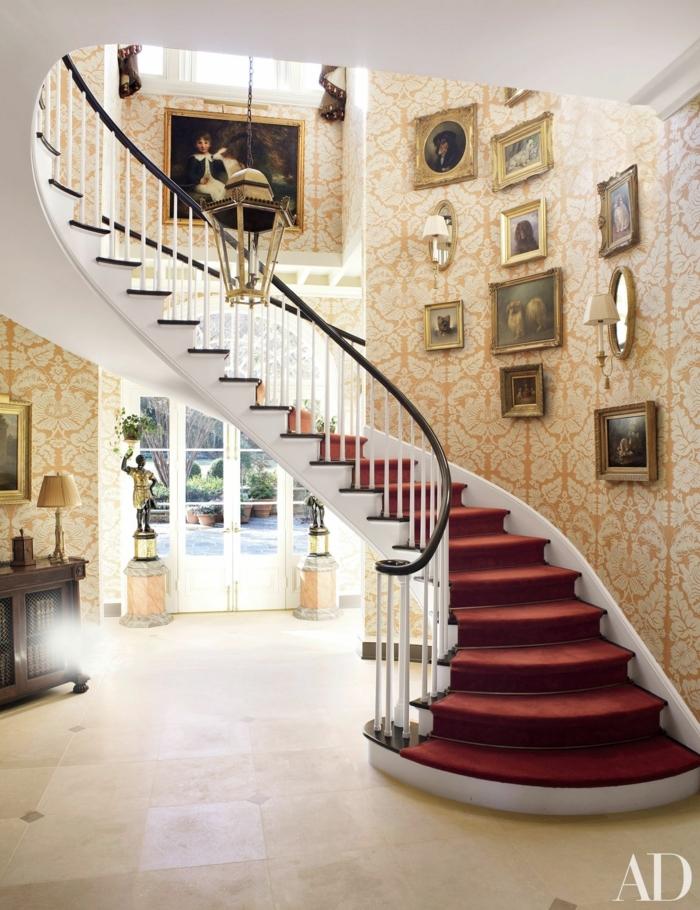 escaleras modernas, casa de lujo, esclareas de caracol con tapizado rojo, papel pintado, techos altos, pinturas con marcos en dorado, entrada con etstauas