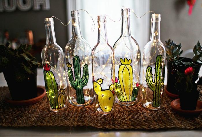 preciosa decoración hecha a mano para el hogar. botellas de cristal dibujadas con cactus con lamparillas dentro