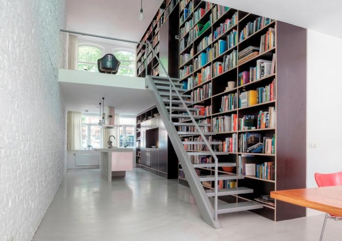 estanterias de pared, cocina y salón, dos plantas, escalera de metal, liberaría grande de madera de suelo a techo, pared ladrillo visto blanco