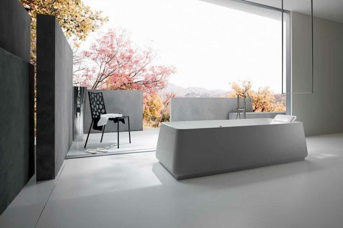 baño grande con ventana, vista al parque, mueble lavabo, bañera rectangular, silla negra, decoración en blanco y negro