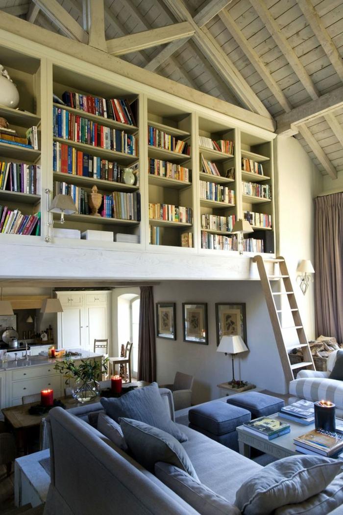 librerias, cocina abierta al salón, balcón interior con biblioteca, escalera de mano, techo triangular con vigas de madera, sofá azul