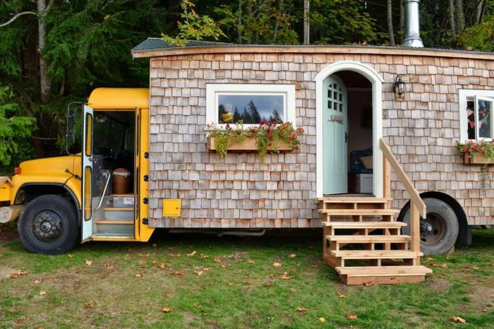 casa cube, autobús escolar transformado en una casa pequeña, escalera de madera y decoración de las ventanas de macetas con flores