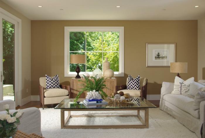 casa rustica, combinacion de colores, salon con ventana grande, paredes en colores terrosos, mesa grande de vidrio, alfombra blanca, sof'a y sillones con cojines en blanco y negro