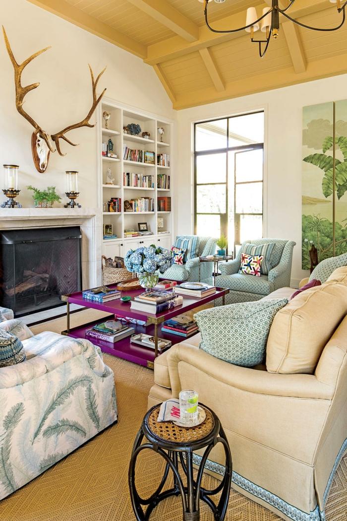 salon rústico, colores para parede, techo de madera, paredes blancos, decoración con cabeza de ciervo, chimenea, sofá con cojines, mesa en lilá con flores