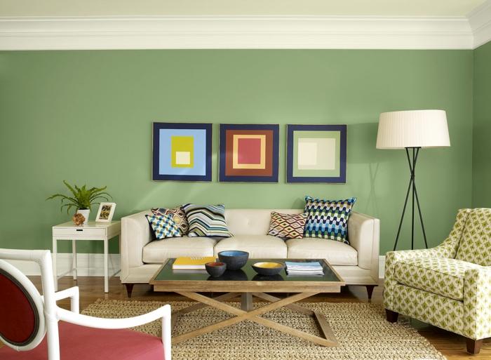 salón vintage, decoración en verde y blanco roto, cuadros geométricos, tapete de mimbre, techo bajo, sofá con cojines, colores para paredes,