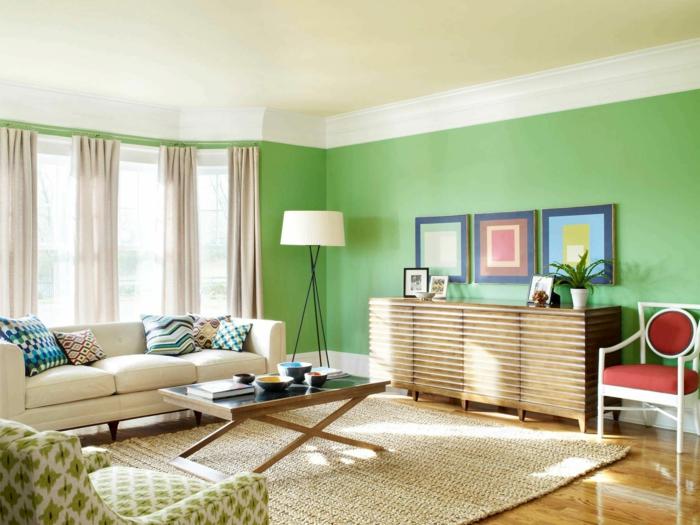 salón con mucha luz natural, colores para paredes, paredes en verde, techo blanco roto, alfombra de mimbre, cuadros geométricos, sofá y mesa de café