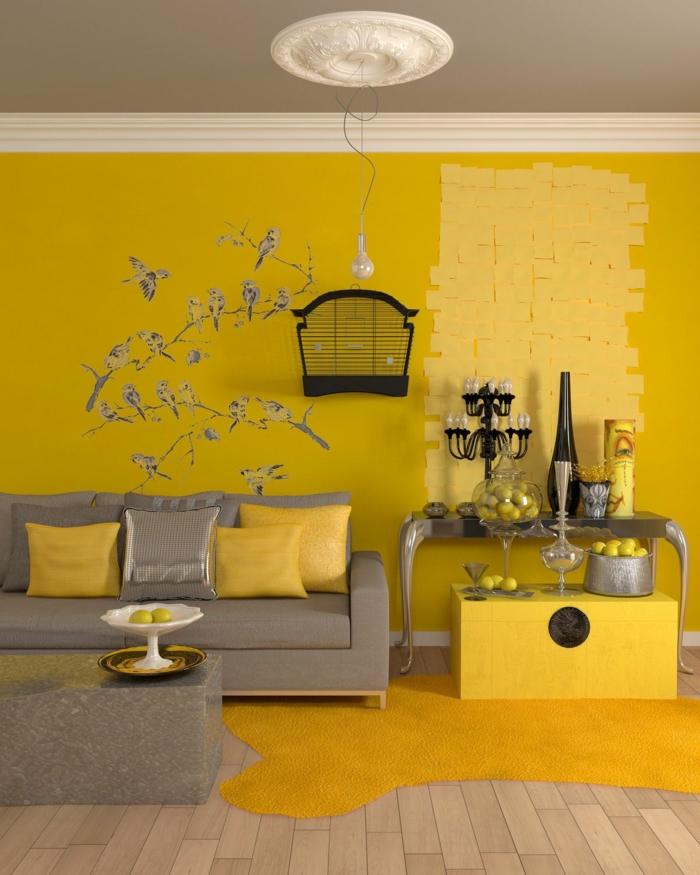 ideas salón, combinacion de colores, techo gris, paredes color mostaza con vinilo de pájaros en ramas, sofá con cojines, suelo con tarima, tapete, candelabro y manzanas