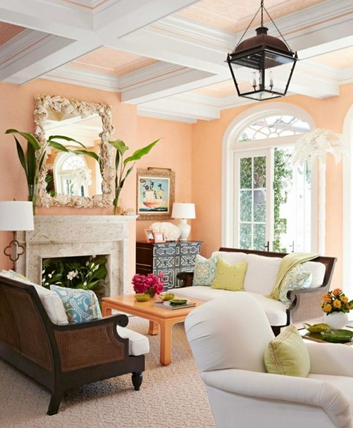 salón con paredes en color melocoton, pintura para paredes, espejo grande, chimenea decorada con plantas, lámpara tipo linterna, ventana grande, mesita coolor naranja, sofá tapizado blanco