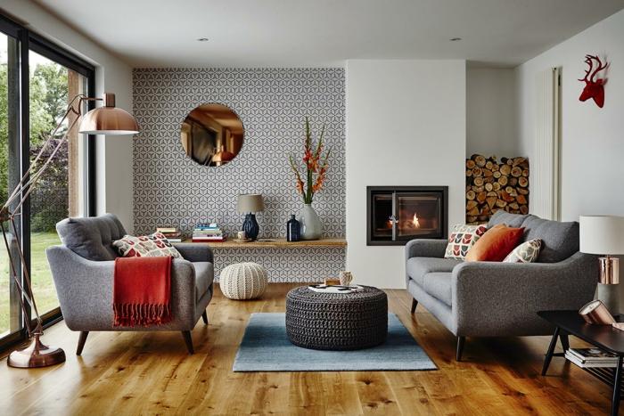 que colores se llevan para pintar un salon, paredes en blanco y negro, chimenea encendida, salon con pared de vidrio, suelo con tarima, sofás gris, cabeza de ciervo
