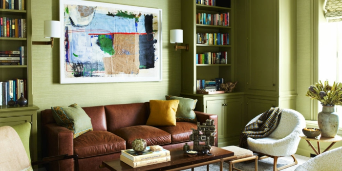 sala de estar estilo clásico, colores para salones, paredes con madera en color pistacho, sofá de piel, estanterías con libros, luz natural
