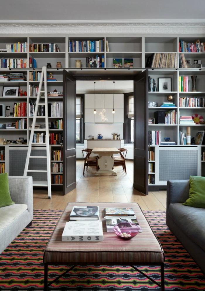 salón con puerta al comedor, estanterias para libros, librería de madera blanca con escalera de mano, alfombra, mesa tapizada, suelo con tarima