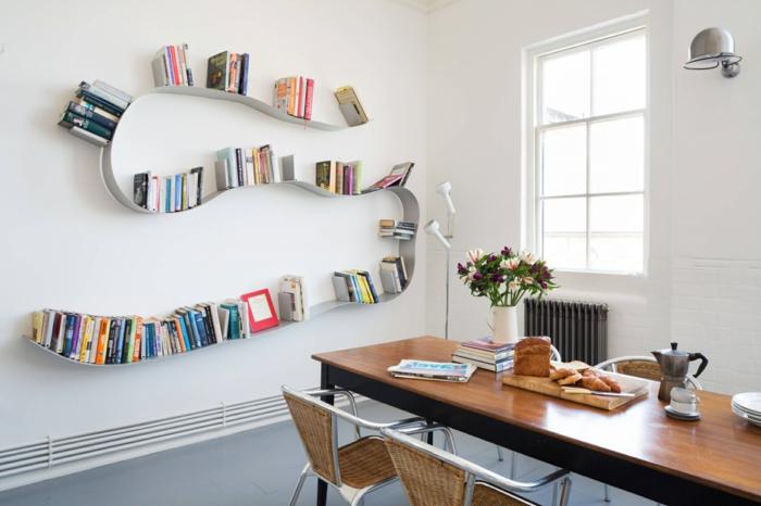 librería moderna de metal en forma de serpiente, estanterias originales, comedor con mesa de madera, paredes blancas