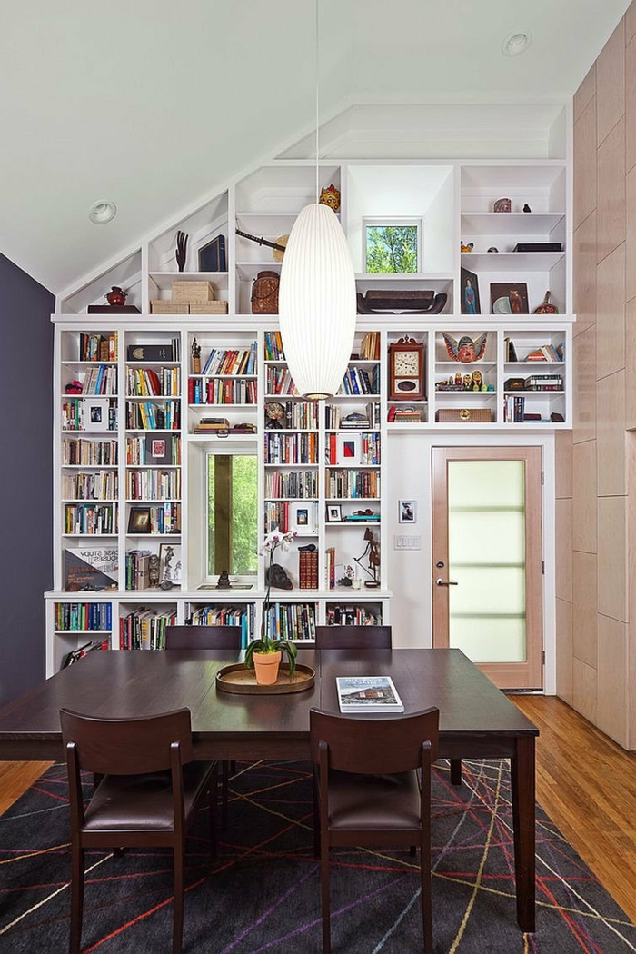 salón comedor con pared irregular, techo con luces empotradas, baldas de madera, librería de suelo a techo de madera blanca, alfombra, mesa de madera oscura, lámpara colgante