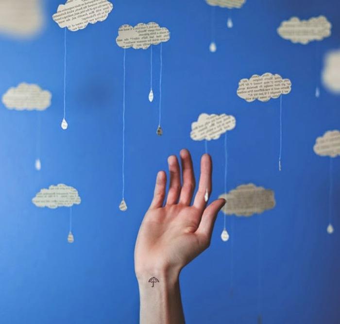 tatuajes pequeños originales, mano con tatuaje minimalista de paraguas en la muñeca, composición con nubes y lluvia de papel