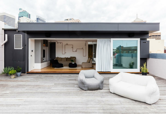 cómo decorar terrazas en estilo moderno minimalista, sillón y sofá tipo puf, suelo de parquet, diseño estilo contemporáneo