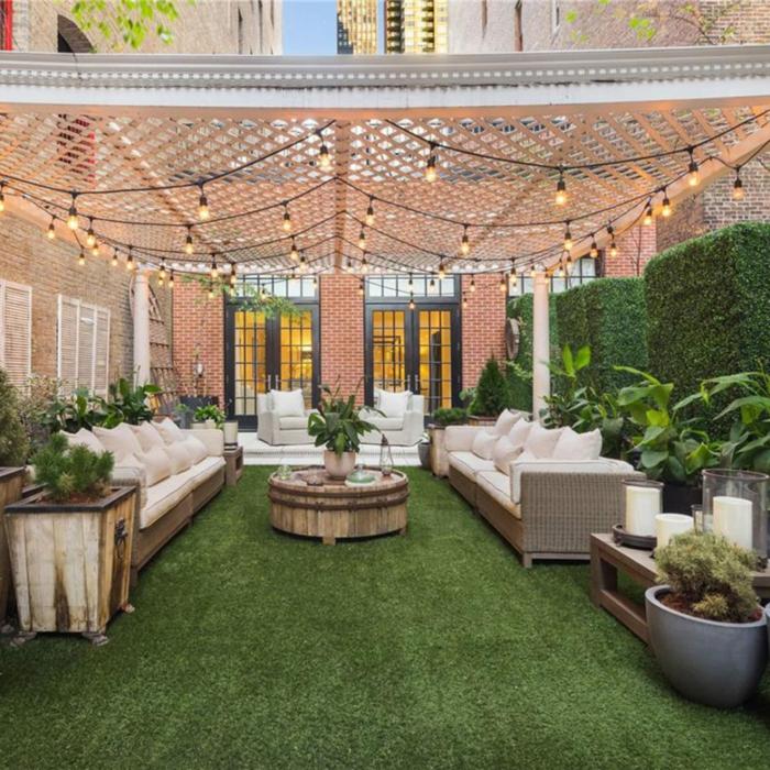 terrazas decoracion con lamparillas, suelo con moqueta en verde, sillones y sofás de mimbre con cobijas y cojines en blanco