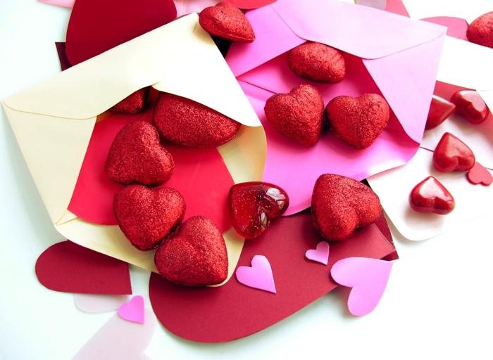 sobres de papel llenos de corazones decorativos en rojo brillante, sorpresas para tu pareja para el día de los enamorados