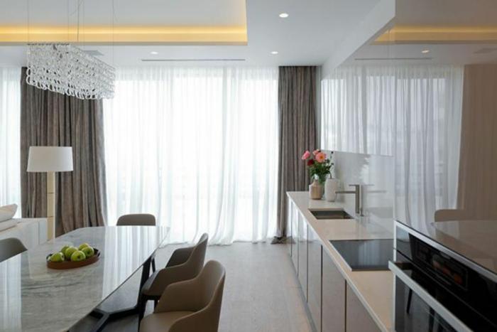 cocinas modernas blancas, cocina abierta al comedor, espacio grande y luminoso decorado en colores claros, cortinas en beige de lino con visillo blanco