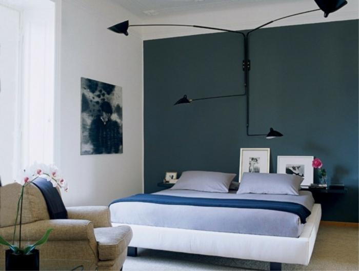 habitación pintada en blanco y azul, con lámpara de diseño muy original, cuadros decorativos modernos