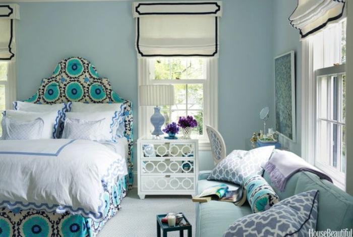 habitación en estilo ecléctico con estores modernos, cama y cuadros vintage, cabecero en arco con estampado en color aguamarina
