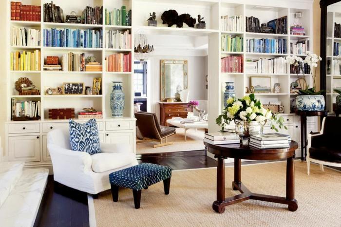 ideas de decoración, librerias, estanterías de madera blancas de suelo a techo, salón acogedor, mesa de madera redonda, flores, tapete de mimbre, librería como separador de ambientes