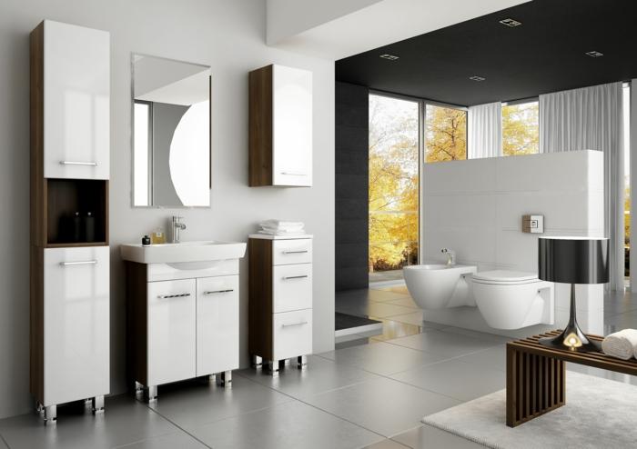 estilo riguroso moderno, decoración en blanco y marrón, mueble lavabo, armarios con patas, ventanales, mesita con lámpara, suelo de baldosas