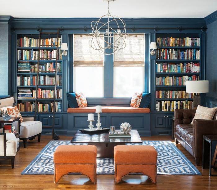 salón clásico, decoración en color naranja y azul, librería de madera azul, ventana con banco con colchoneta y cojines, alfombra. sofá de piel, estanterias para libros