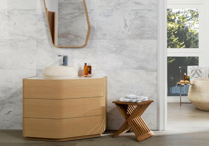 baño moderno, muebles auxiliares, lavabo pequeño redondo, mueble de madera con cajones sin asa, silla, espejo grande, paredes de mármol