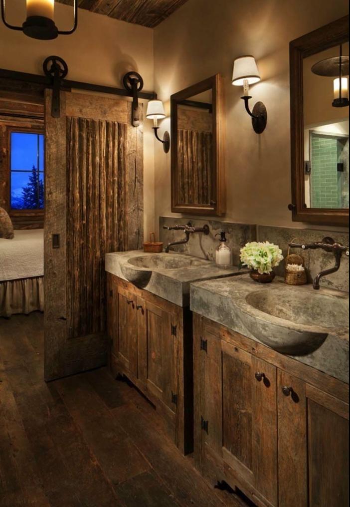 ambiente rústico con estanterias para baños, puerta deslizante, armarios de madera y lavabos de hormigón, lámparas vintage