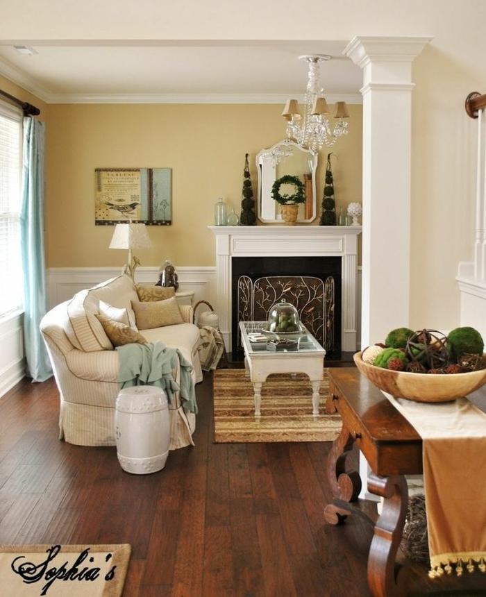 salón decorado en estilo clásico con chimenea, pintura para paredes, colores arena y blanco, suelo con tarima, mesa comedor de madera, lámpara de araña, ventanas con cortinas azules