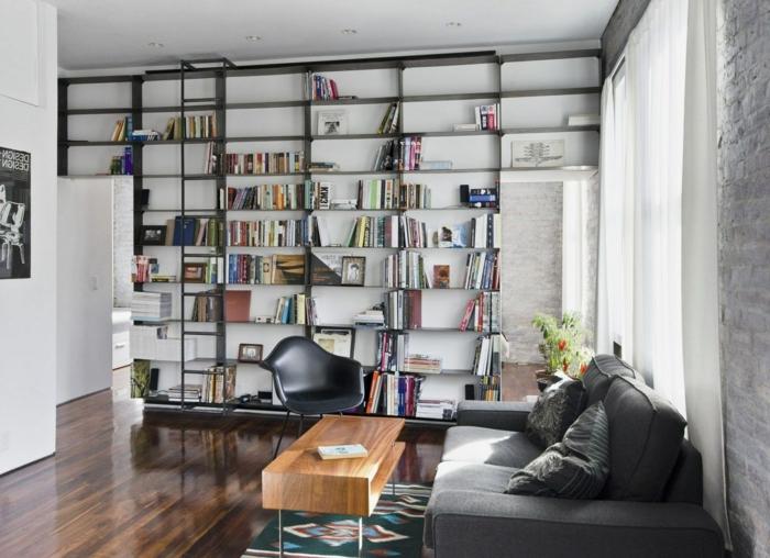 estilo contemporaneo, librería de suelo a techo color negro con escalera movible, mesa de madera, sillón de plástico, sofá gris, baldas de madera