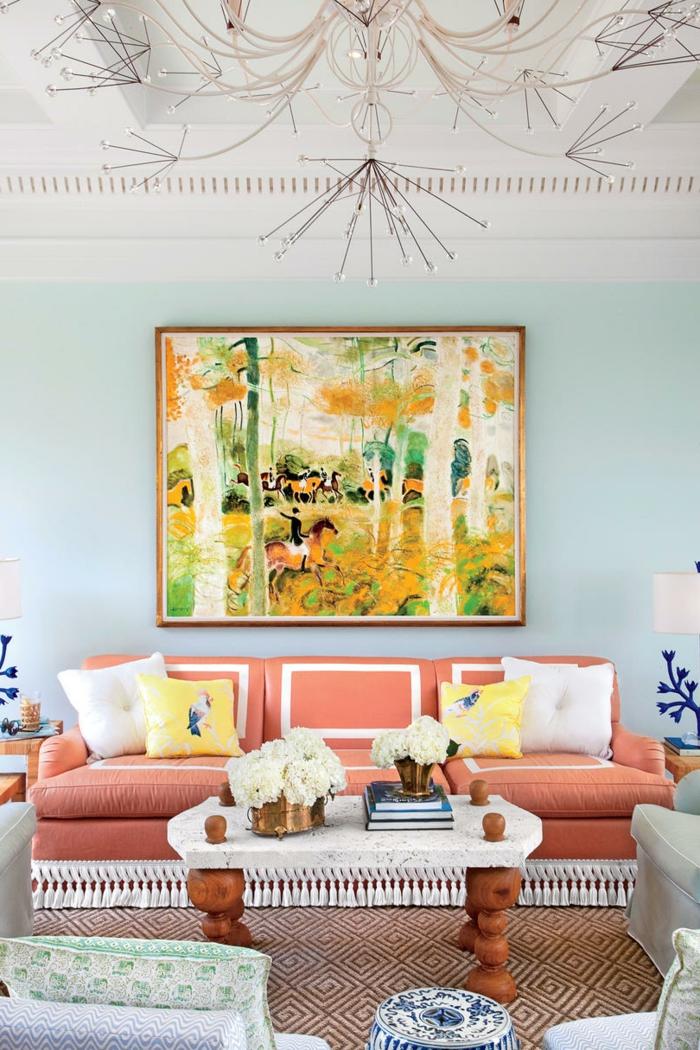 colores para pintar un salon, salon en colores pasteles, sofá melocotón con flecos blancos, pared azul celeste, cuadro grande, mesa de mármol y madera