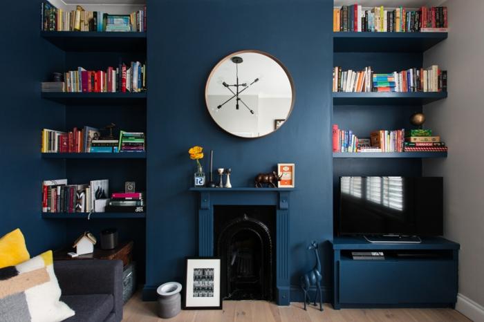 salon pequeño, colores para paredes, chimenea y librerías, paredes azul oscuro, espejo redondo grande, flor amarilla, sofá con cojines