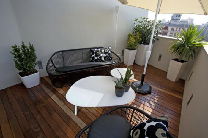 diseño moderno de una terraza pequeña, terrazas decoracion en blanco y negro, mesa blanca de tres patas, suelo de madera