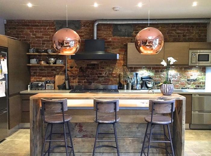 lámparas en estilo de los años 80 en color cobrizo, cocina moderna en estilo industrial con muebles de efecto desgastado