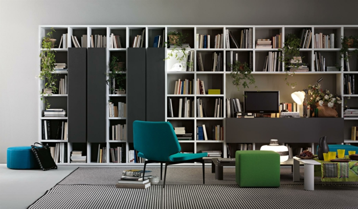 salón moderno, librería de madera blanca, decoración en blanco, negro y gris, silla azul, librerias, alfombra rayada, mesilla de café baja