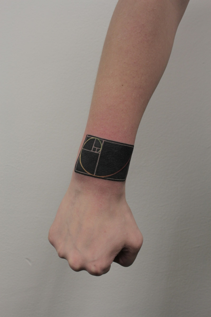 tatuajes en la muñeca, diseño de tatuaje masculina, brazalete grande en ngro con figuras geométricas, puño cerrado