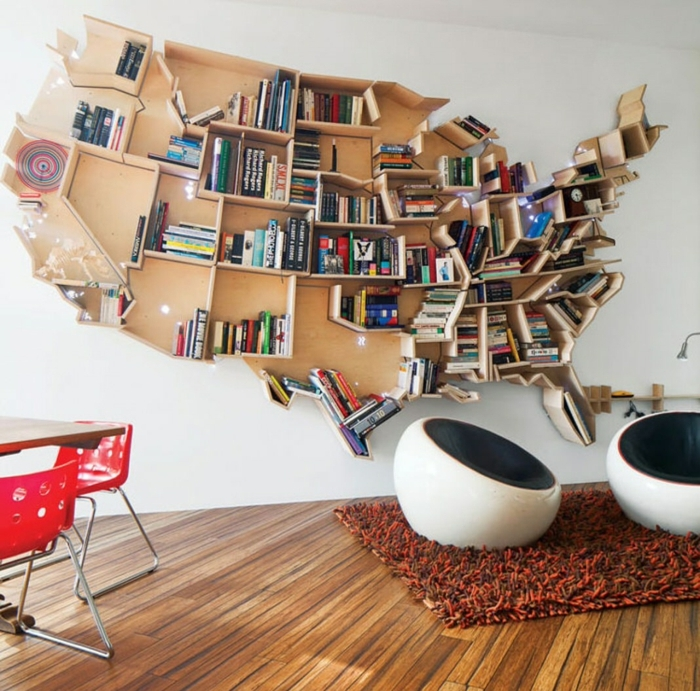 librería original en forma de mapa de Estados Unidos, baldas de madera, salón moderno con tapete peludo y mesa con sillas rojas de plástico y metal