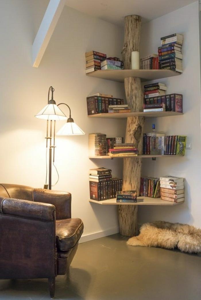 estantería original en forma de árbol con tronco natural, sillón tapizado de piel, lámpara blanca de metl, paredes blancas, librerías