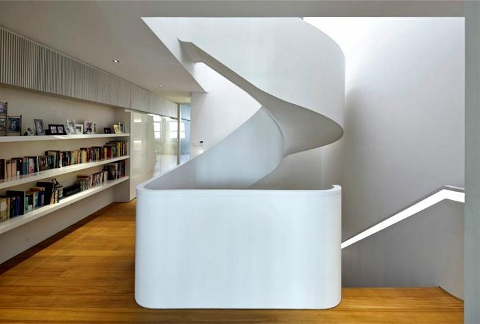 escaleras de madera, escalera de caracol extravagante de hormigón. pared con estantes con libros y foros, suelo laminado