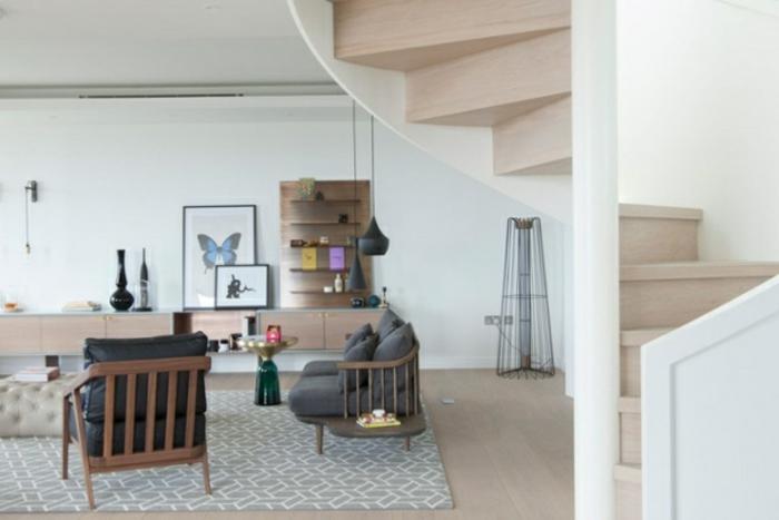 escaleras de madera, salón con muebles en madera clara y alfombra, escaleras de caracol con barandilla blanca