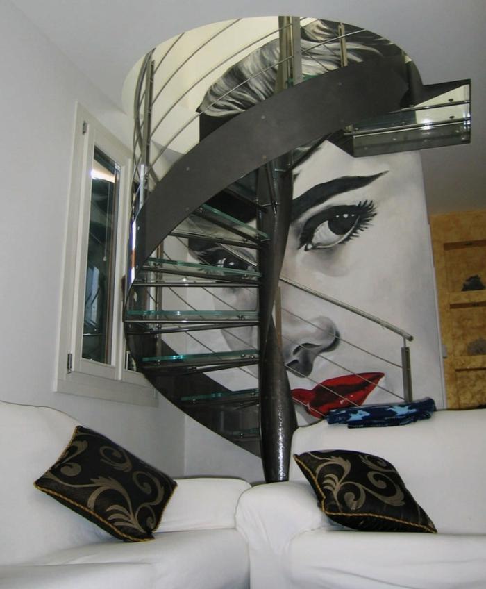 escaleras de caracol, salón con muebles en blanco, vinilo grande en la pared, cara de mujer con labios rojos, escalera de caracol con escalones de vidrio y barandilla de metal