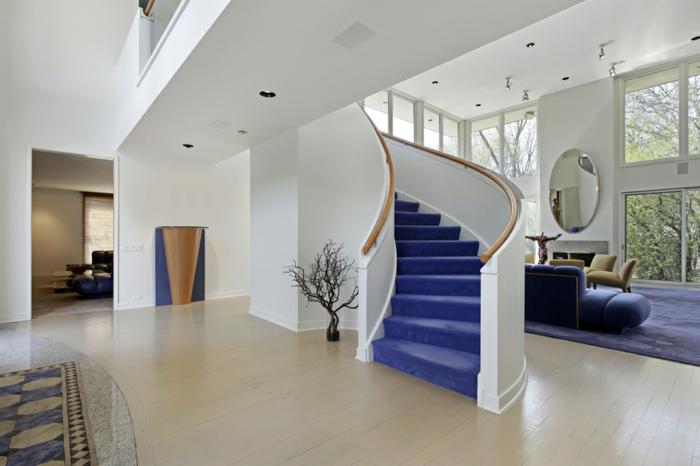 escalera metalica, salón en blanco y azul, decoración moderna, escalera de caracol de hormigón y madera con escalones tapizados