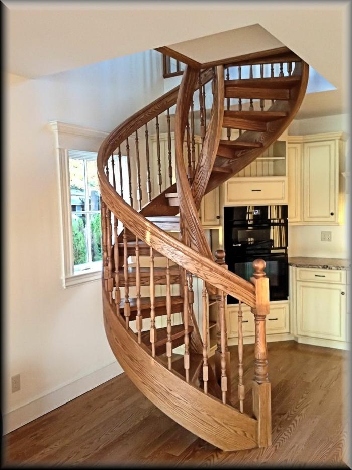escaleras de madera. cocina vintage con muebles beige, suelo laminado, ventana pequeña, escalera de caracol de madera