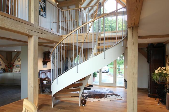 escaleras de interior, casa con pilares de madera y balcón interior, escalera de caracol con barandilla de metal y madera